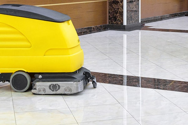 Tile floor being cleaned with professional floor cleaner.